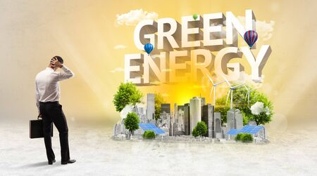 Rear view of a businessman standing in front of GREEN ENERGY inscription, Environmental protection concept