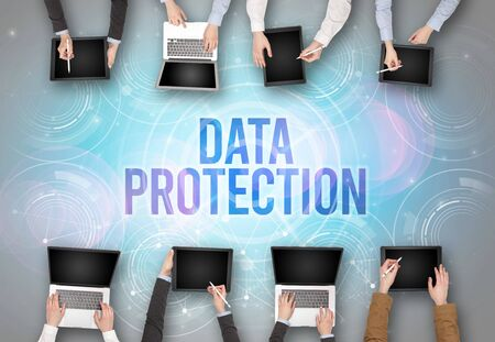Group of people in front of a laptop with DATA PROTECTION insciption, web security concept