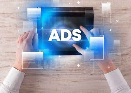 Close-up of a hand holding tablet with ADS abbreviation, modern technology concept