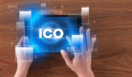Close-up of a hand holding tablet with ICO  abbreviation, modern technology concept Фото со стока