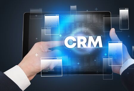 Close-up of a hand holding tablet with CRM  abbreviation, modern technology concept