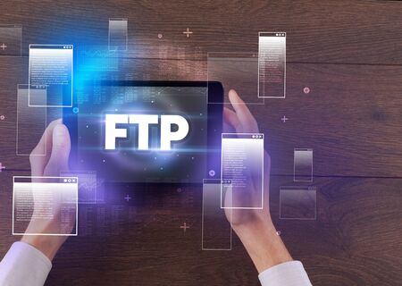 Close-up of a hand holding tablet with FTP  abbreviation, modern technology concept