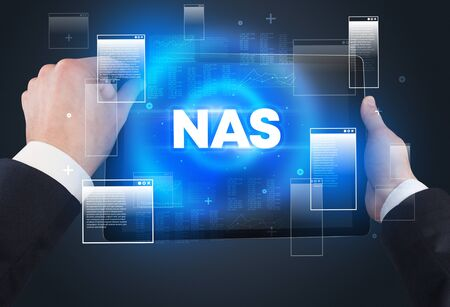 Close-up of a hand holding tablet with NAS  abbreviation, modern technology concept