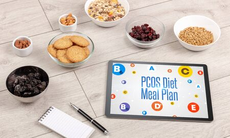 Healthy Tablet Pc compostion with PCOS Diet Meal Plan inscription, weight loss concept Stock Photo