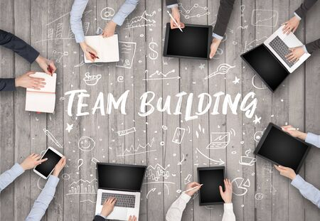 Group of business people working in office with TEAM BUILDING inscription, coworking concept