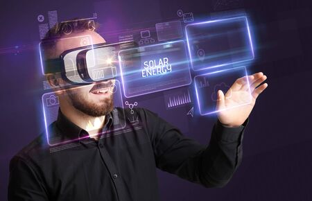 Businessman looking through Virtual Reality glasses with SOLAR ENERGY inscription, new technology concept