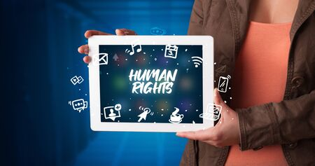 Young business person working on tablet and shows the inscription: HUMAN RIGHTS