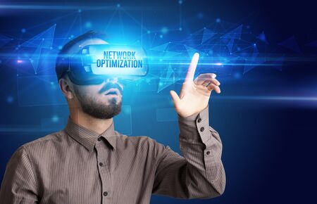 Businessman looking through Virtual Reality glasses with NETWORK OPTIMIZATION inscription, cyber security concept
