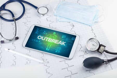 Tablet pc and doctor tools with OUTBREAK inscription, coronavirus concept Stock Photo