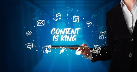 Young business person working on tablet and shows the inscription: CONTENT IS KING