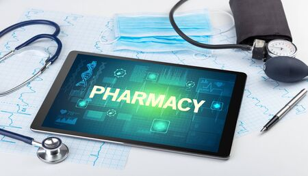 Tablet pc and medical stuff with PHARMACY inscription, prevention concept 免版税图像 - 150260838