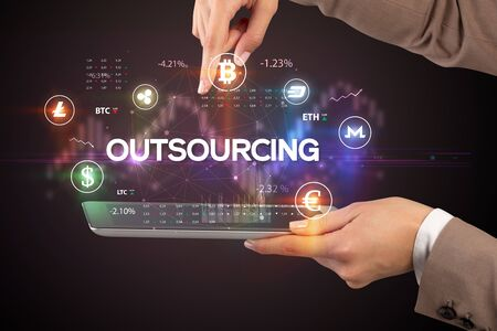 Close-up of a touchscreen with OUTSOURCING inscription, business opportunity concept