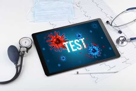 Tablet pc and doctor tools on white surface with TEST inscription, pandemic concept 免版税图像 - 150261014