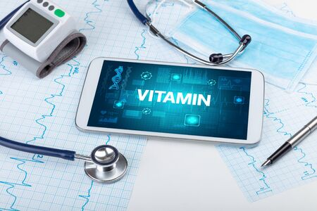 Tablet pc and medical stuff with VITAMIN inscription, prevention concept 免版税图像 - 150261033