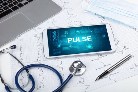 Tablet pc and medical stuff with PULSE inscription, prevention concept 免版税图像