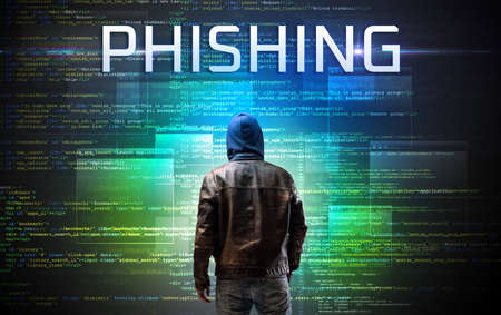 Faceless hacker with PHISHING inscription on a binary code background