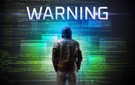 Faceless hacker with WARNING inscription on a binary code background Reklamní fotografie