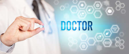 Close-up of a doctor giving you a pill with DOCTOR inscription, medical concept
