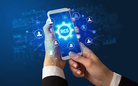 Female hand holding smartphone with RCS abbreviation, modern technology concept Stock fotó