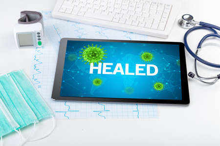 Close-up view of a tablet pc with HEALED inscription, microbiology concept