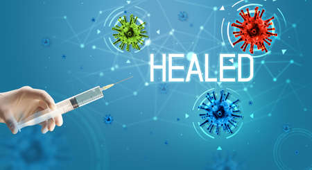 Syringe, medical injection in hand with HEALED inscription, coronavirus vaccine concept