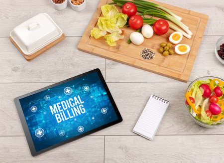 MEDICAL BILLING concept in tablet pc with healthy food around, top view