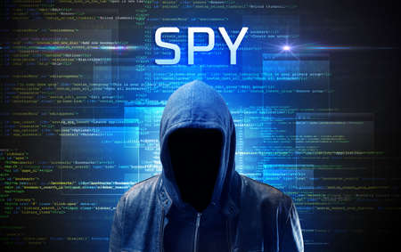 Faceless hacker with SPY inscription on a binary code background
