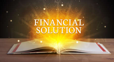 FINANCIAL SOLUTION inscription coming out from an open book, educational concept Stockfoto