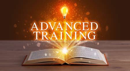 ADVANCED TRAINING inscription coming out from an open book, educational concept Stockfoto