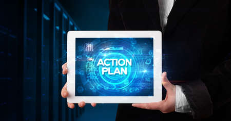 Young business person working on tablet and shows the inscription: ACTION PLAN, business concept Stockfoto