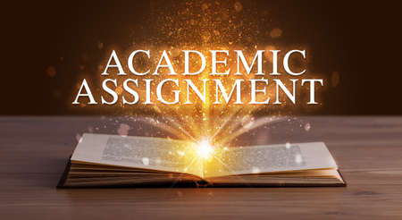 ACADEMIC ASSIGNMENT inscription coming out from an open book, educational concept Stockfoto