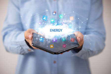 Businessman holding a foldable smartphone with ENERGY inscription, technology concept
