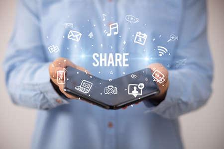 Businessman holding a foldable smartphone with SHARE inscription, social media concept Foto de archivo