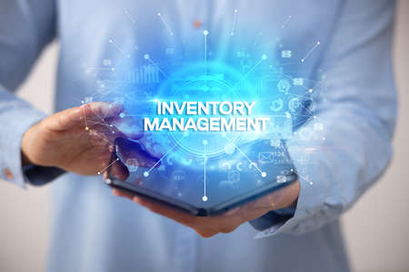 Businessman holding a foldable smartphone with INVENTORY MANAGEMENT inscription, new business concept Foto de archivo