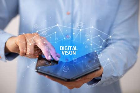 Businessman holding a foldable smartphone with DIGITAL VISON inscription, new technology concept