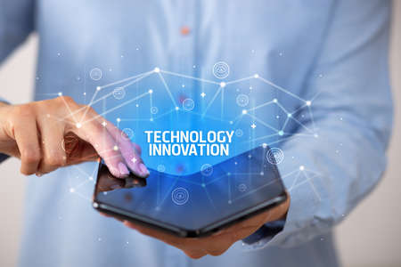Businessman holding a foldable smartphone with TECHNOLOGY INNOVATION inscription, new technology concept