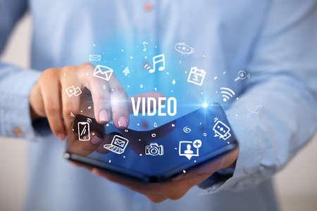 Businessman holding a foldable smartphone with VIDEO inscription, social media concept Foto de archivo