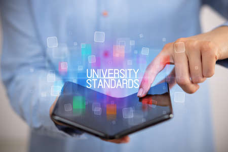 Young man holding a foldable smartphone with UNIVERSITY STANDARDS inscription, educational concept