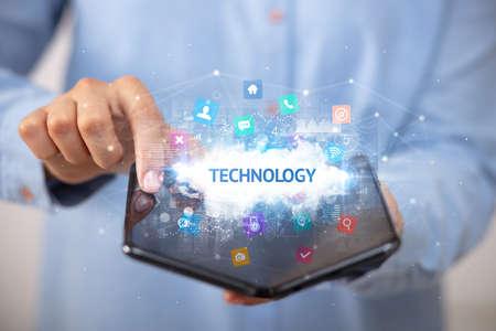 Businessman holding a foldable smartphone with TECHNOLOGY inscription, technology concept Foto de archivo