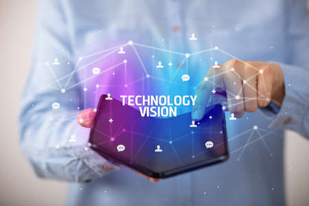 Businessman holding a foldable smartphone with TECHNOLOGY VISION inscription, new technology concept