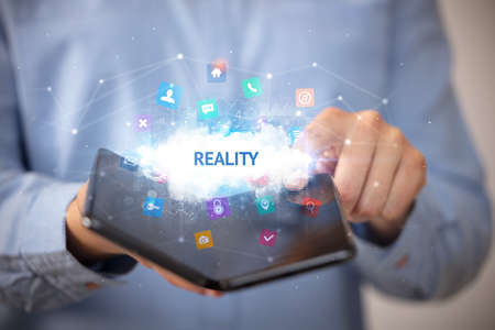 Businessman holding a foldable smartphone with REALITY inscription, technology concept