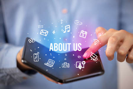 Businessman holding a foldable smartphone with ABOUT US inscription, social media concept