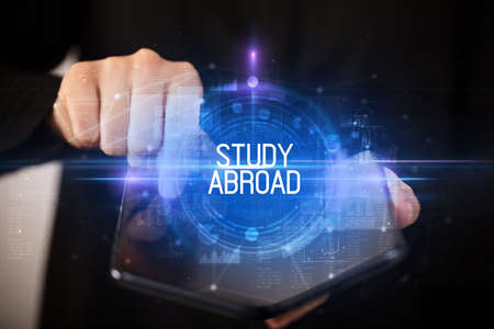 Young man holding a foldable smartphone with STUDY ABROAD inscription, educational concept Stockfoto