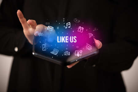 Businessman holding a foldable smartphone with LIKE US inscription, social media concept Foto de archivo