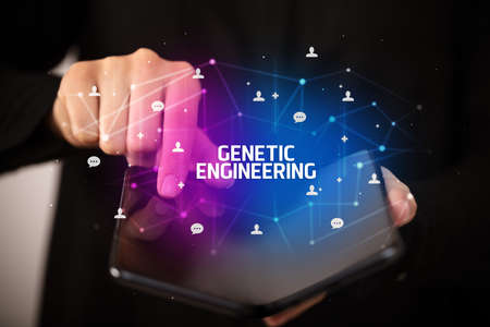 Businessman holding a foldable smartphone with GENETIC ENGINEERING inscription, new technology concept