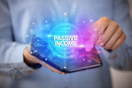 Businessman holding a foldable smartphone with PASSIVE INCOME inscription, new business concept