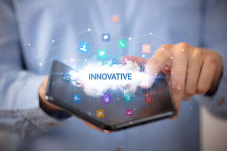 Businessman holding a foldable smartphone with INNOVATIVE inscription, technology concept Foto de archivo