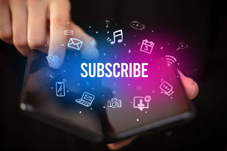 Businessman holding a foldable smartphone with SUBSCRIBE inscription, social media concept