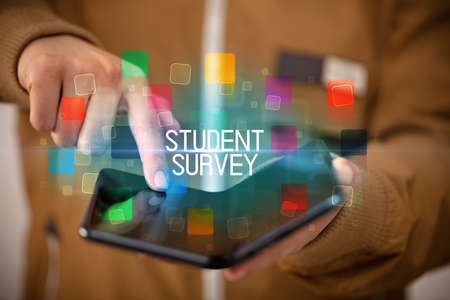 Young man holding a foldable smartphone with STUDENT SURVEY inscription, educational concept