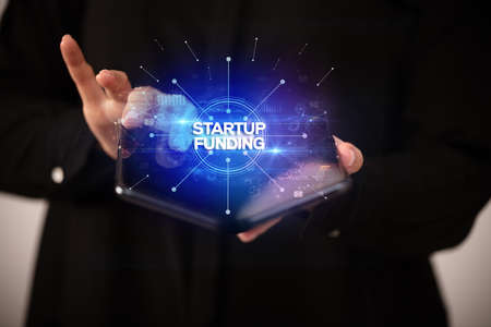 Businessman holding a foldable smartphone with STARTUP FUNDING inscription, new business concept